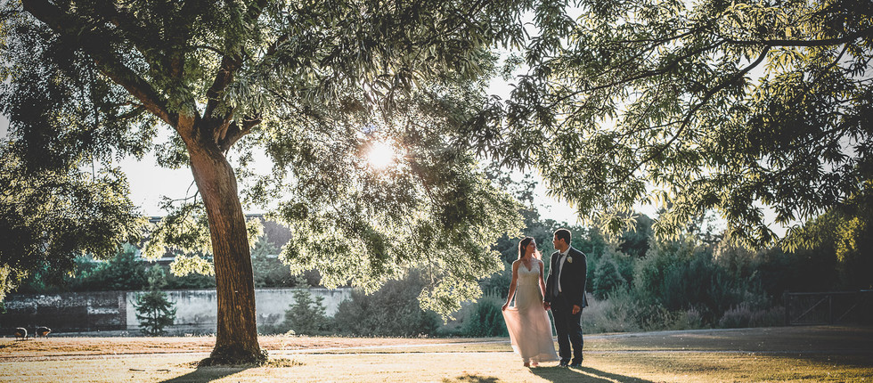 Couple walk under tree in Syon house
