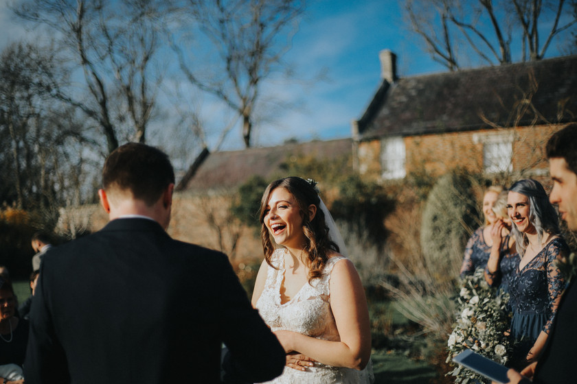 bride laughs with groom at wedding alter outside of wadhurst castle