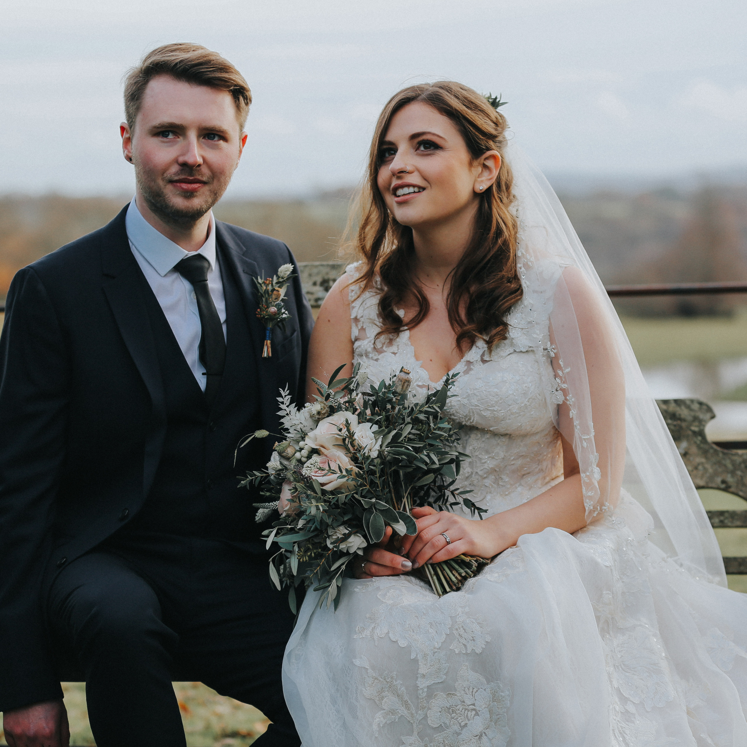 Bride and groom sit on bench and look into the distance at wadhurst castle wedding