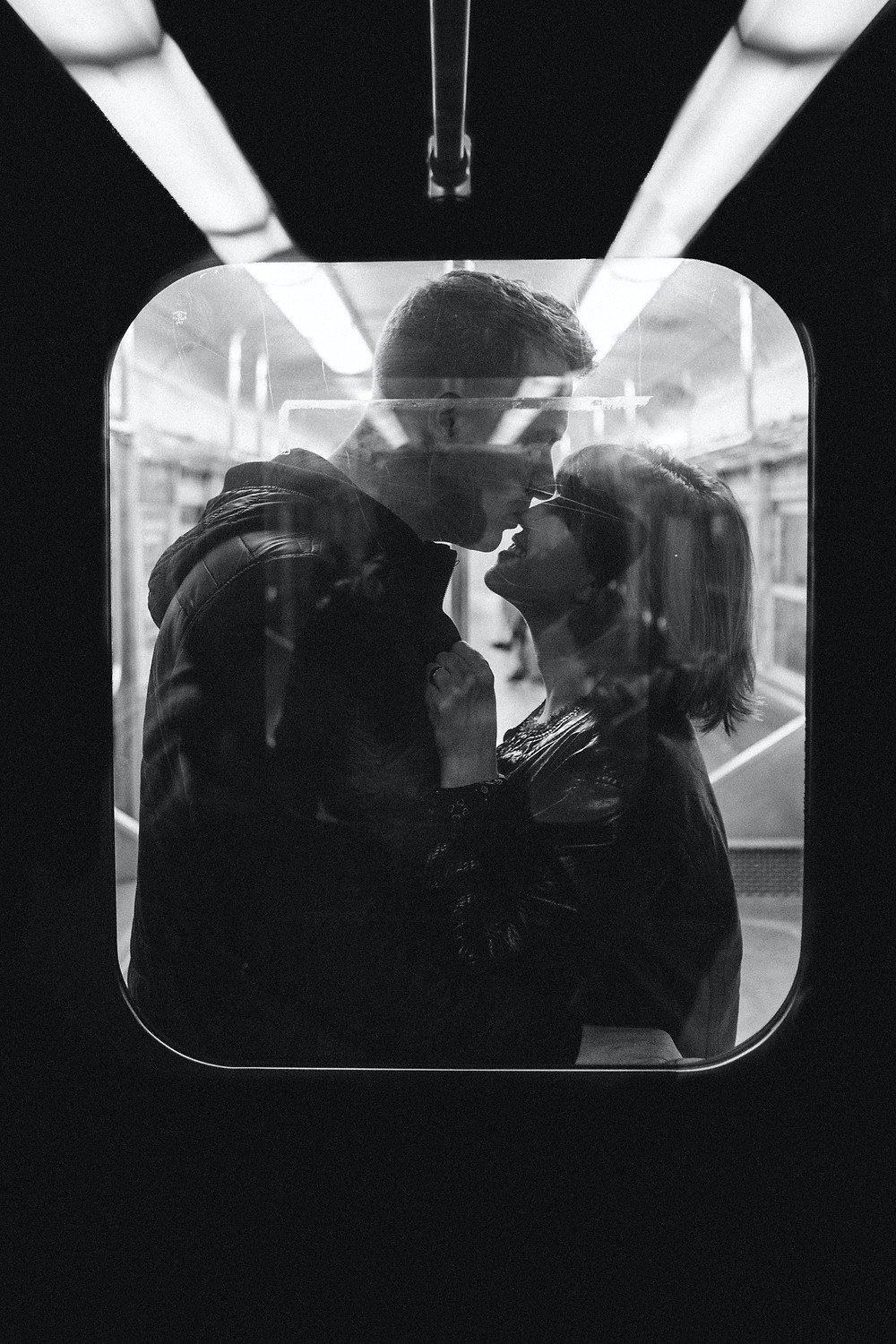 Black and white couple portrait through the window on the tube