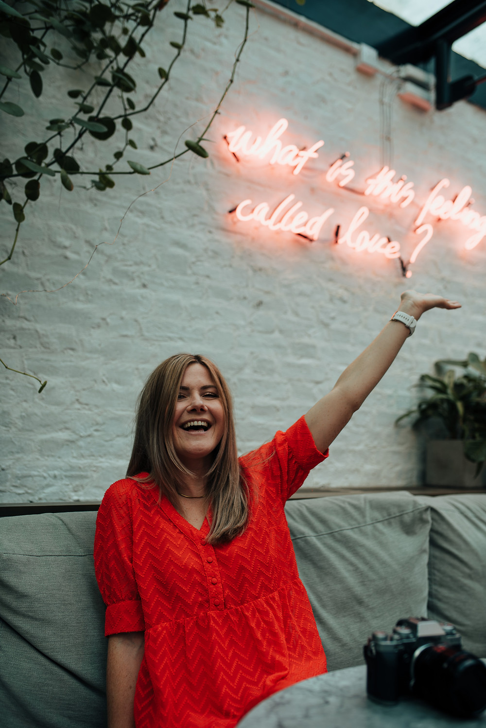 Photo of Tash Busta Photography looking delighted under neon sign about love