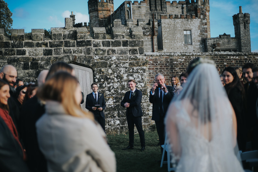 Groom looks emotionally at bride as she walks down the aisle on wadhurst castle grounds