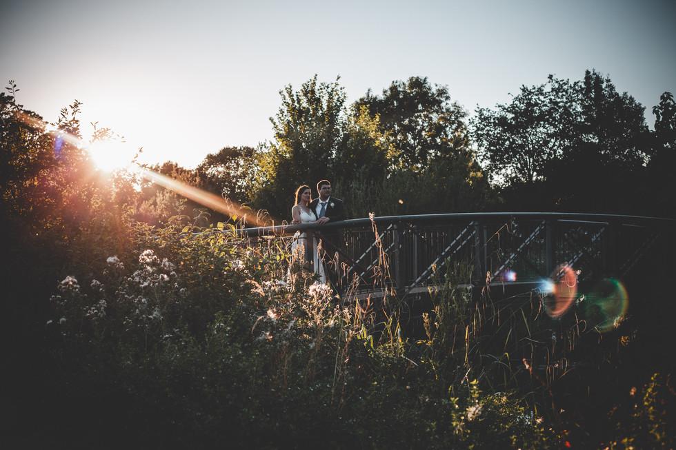 Creative wedding photography: Couple look across from bridge at Syon House