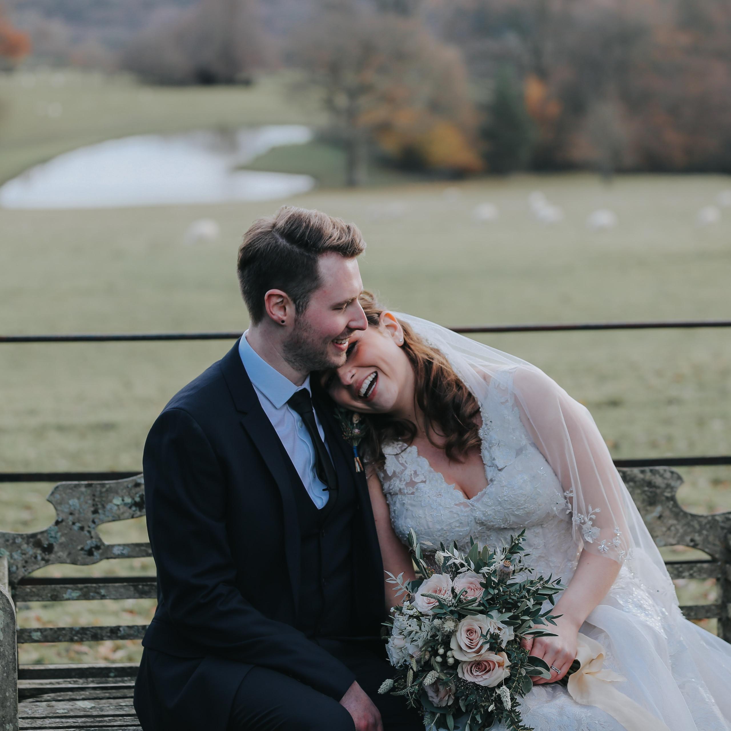 Bride laughs and leans into grroms shoulder at wedding at Wadhurst Castle