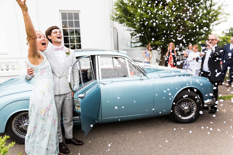 London wedding photography of bride and groom having confetti thrown next to classic car