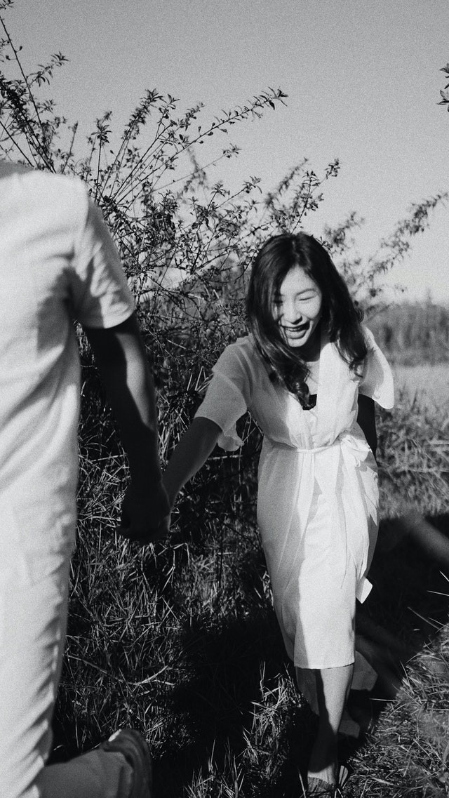 black and white photo of man holding Asian girls hand while laughing