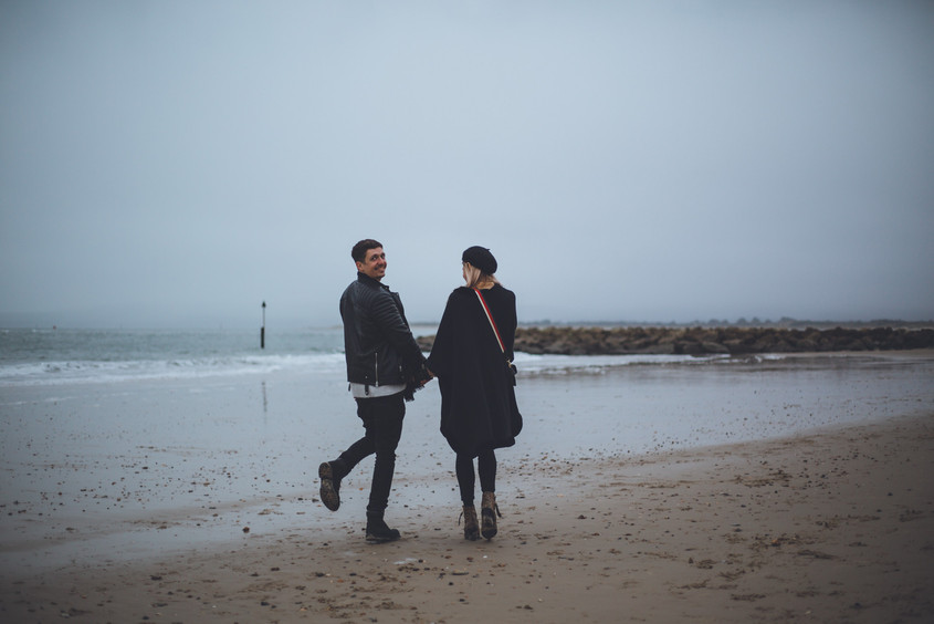 Photo by wedding photographer of man and woman holding hands during couples shoot on Sandbanks beach