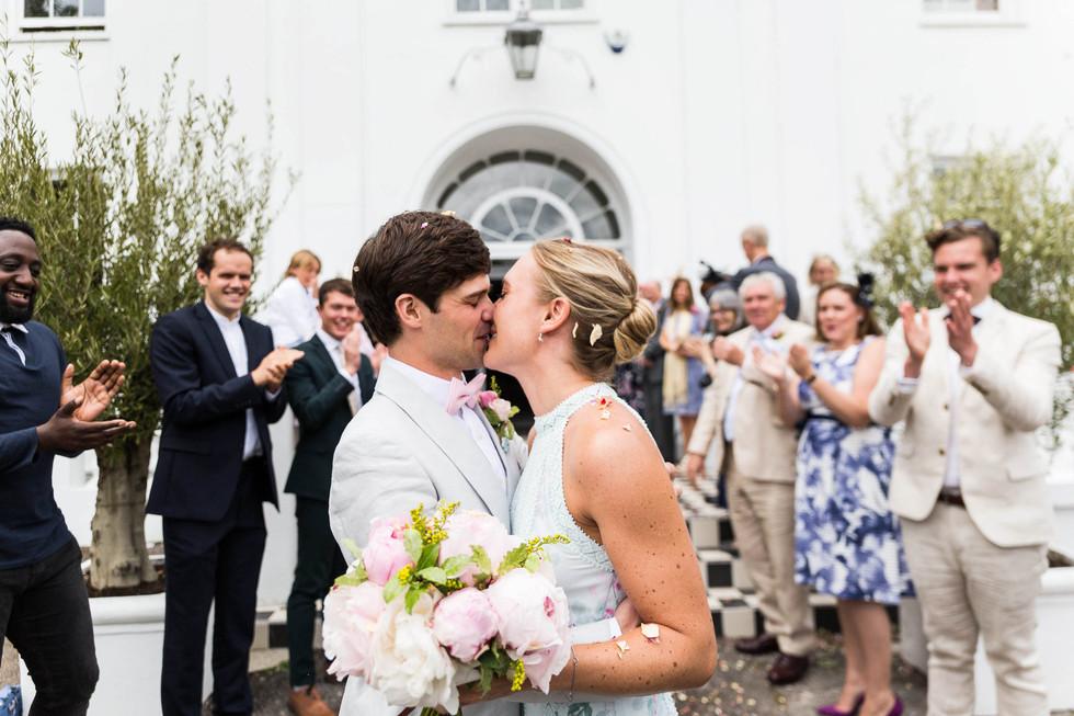 Wedding Photographer London. Bride and groom kiss outside Belair house