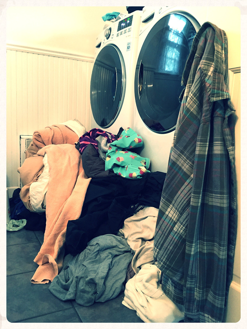 Laundry room piled with clothes to be washed.