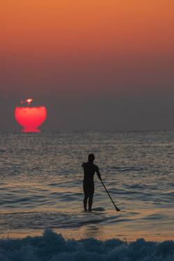 素晴らしい朝日を見ながらの海でのSUP