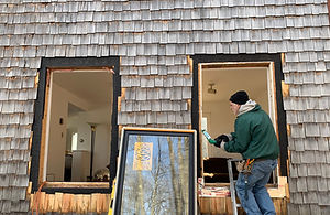 Man installing Sierra Pacific Casement Window into frame opening on house with wood shake shingles