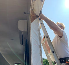 Installer sealing tarp on window frame opening in home with white ceiling on sunny day