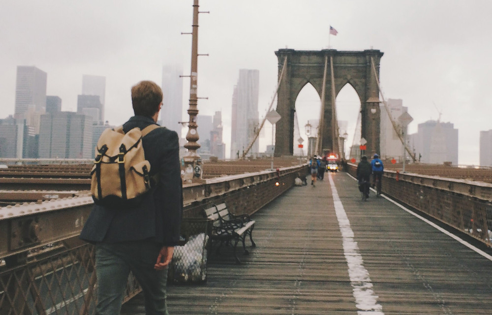 Man with pack back pack crossing bridge.