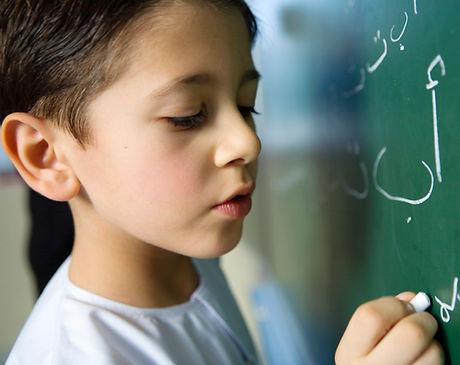 Niño escribiendo en una pizarra