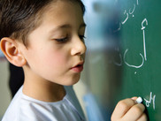Garçon écrivant sur un tableau noir
