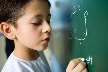 Junge, der auf eine Tafel schreibt