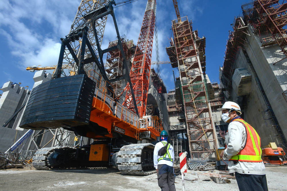 construction workers in PPE stand in front of a sustainable construction site. A mega structure is being built with giant machinery