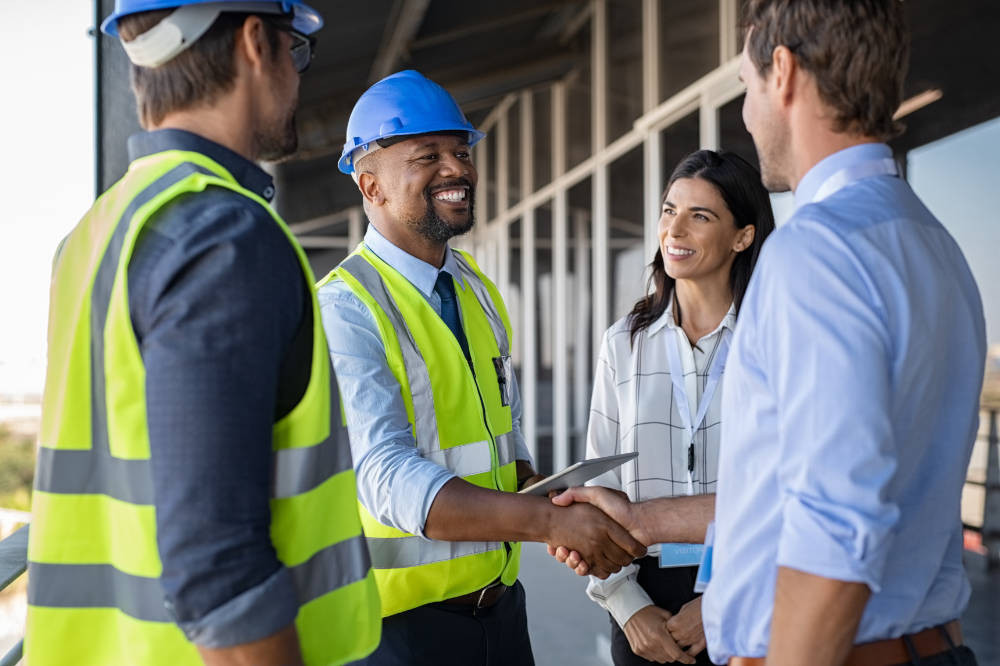 contractors shake hands with their clients at the beginning of an office refurbishment project