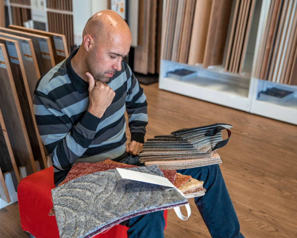 a man chooses carpet for his office refurbishment project by looking at samples