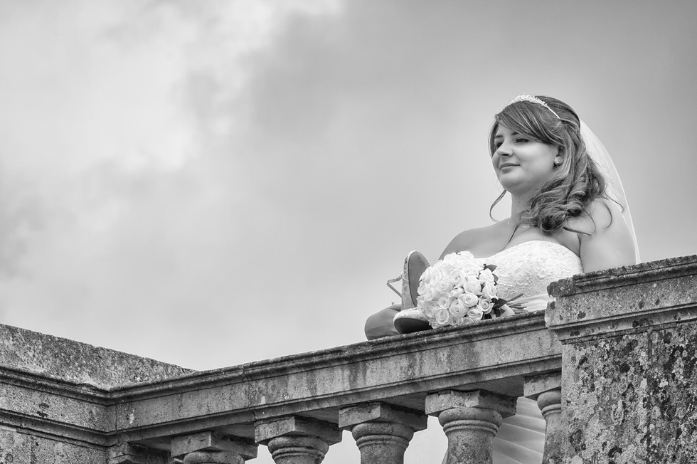 Bride with her bouque on a stone bridge looking into the distance.