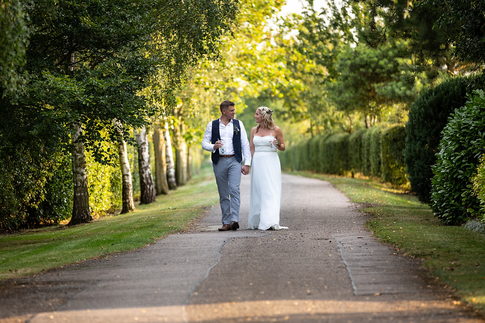 Bride & Groom walking down an English country lane hand in hand.