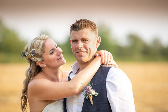 Brdie and Groom in a wheat field embracing.