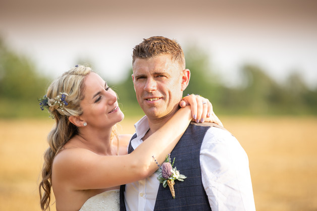 Bride and Groom in a wheat field at the Golden Hour.