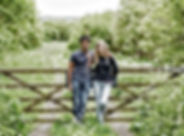 Engagement couple leaning on a five bar gate in a filed.