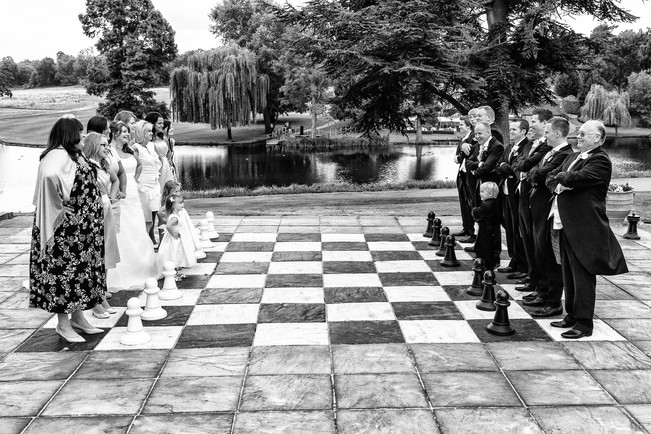 Wedding guest being chess peaces on a large outside chess board.