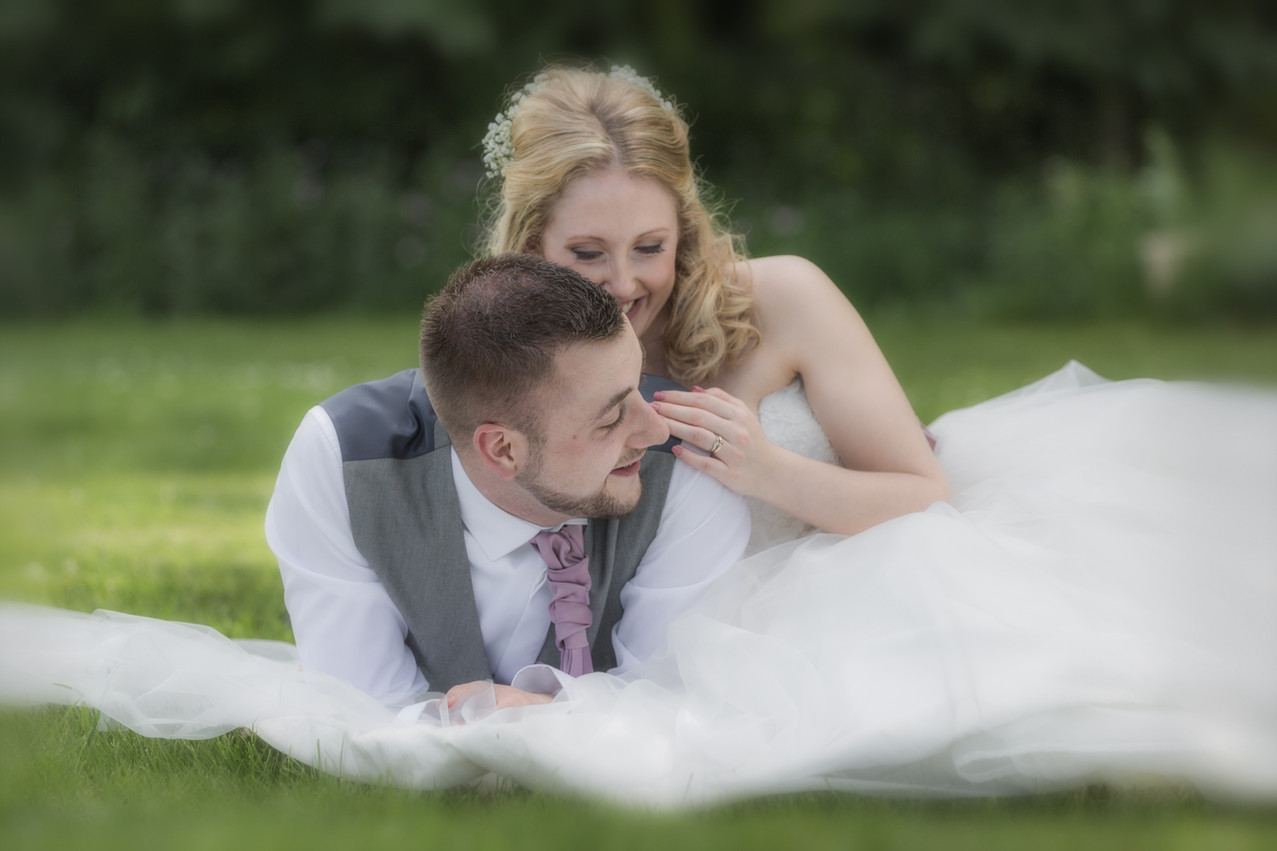 Bride and Groom laying on the grass in an English Statley Home