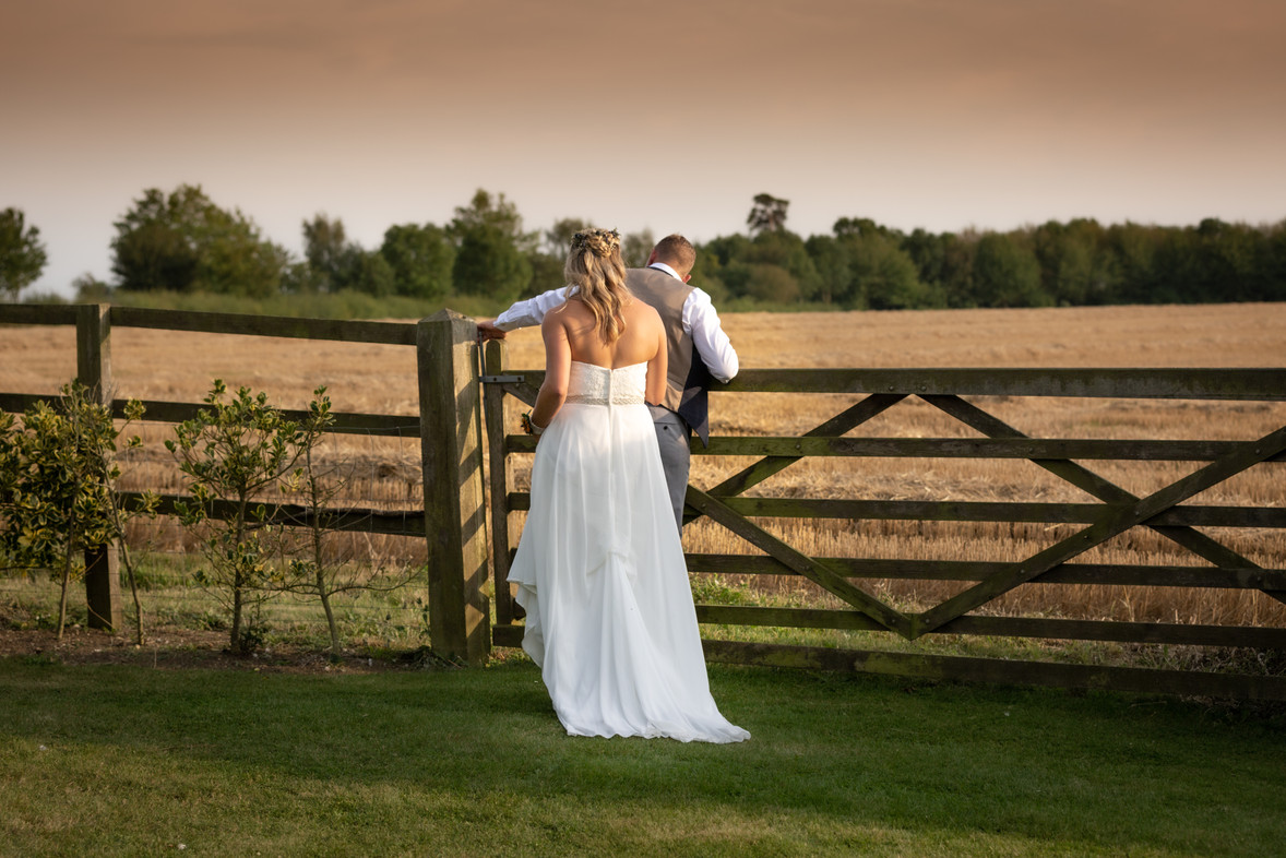 Bride and Groom opening a 5 bar gate into a wheat field at sunset.