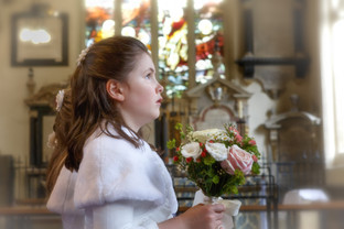 Flower girl with a bouque in a church with stained glass windows.