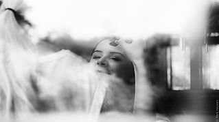 Picture taken through a glass window of the Bride getting her makeup done on her Wedding Day.