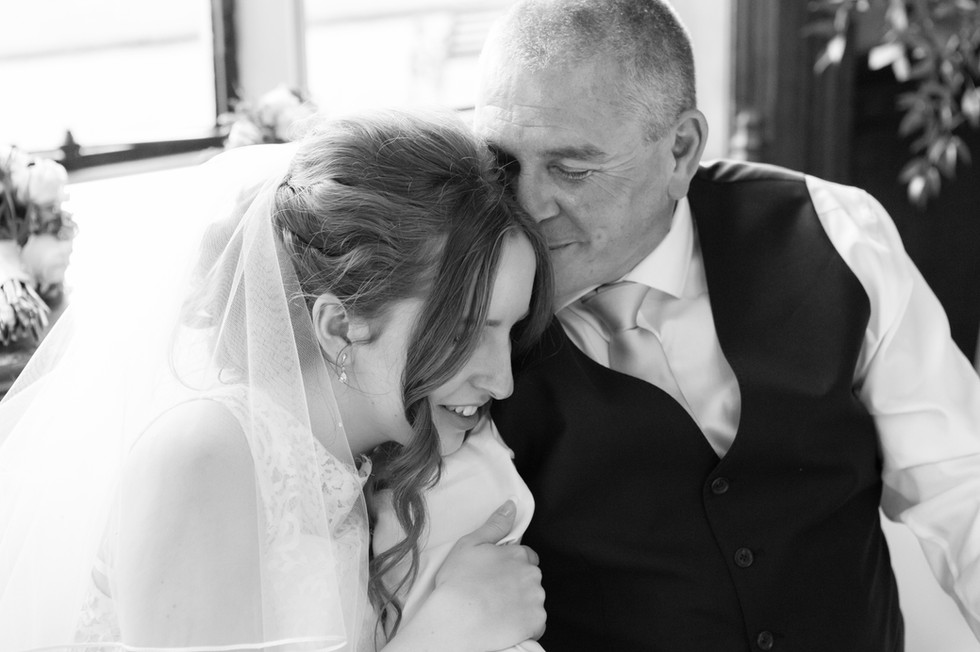 Bride holding her father in a loveing embrace.