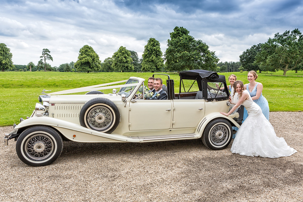 Bride and bridemaids pushing the groom and best man in a vintage car at The House at Shuttleworth
