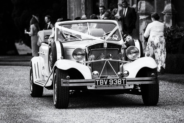 Bride and Groom being driven in a vintage car.