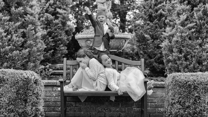 Flower girls and page boy acting out on a park bench.