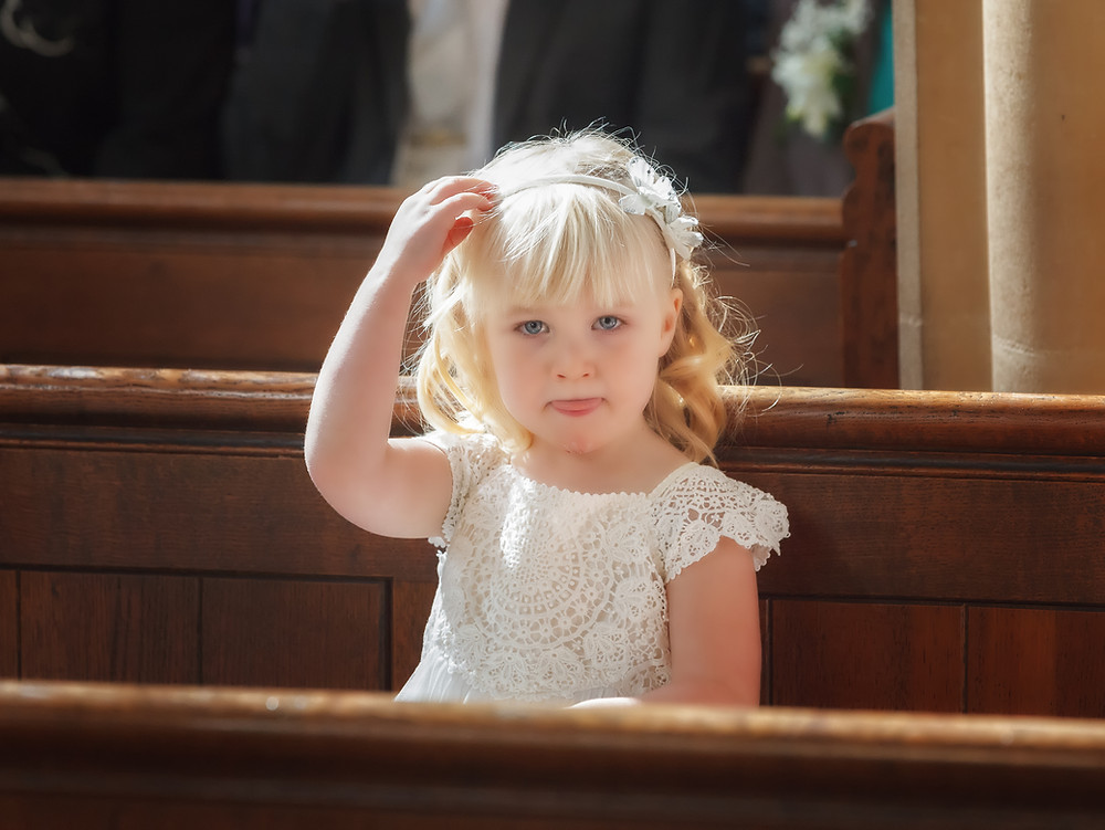 Flower girl sat on a church pew with sunlight on her face.