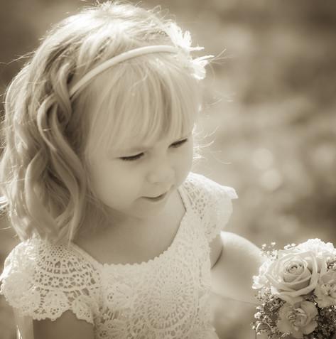 Flower girl with golden hair holding her flowers.