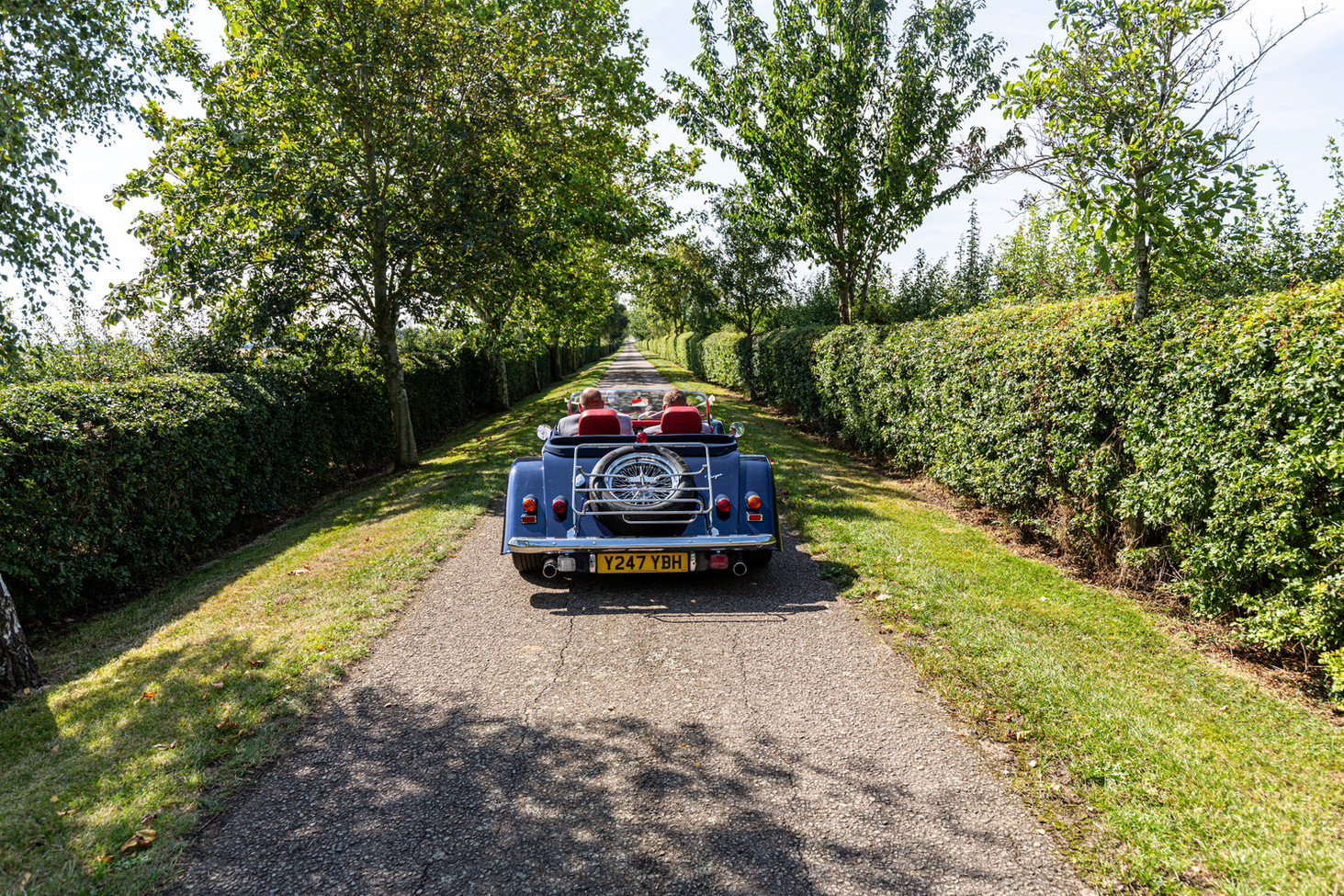 Groom and Bestman in a Morgan sports car on a country lane.