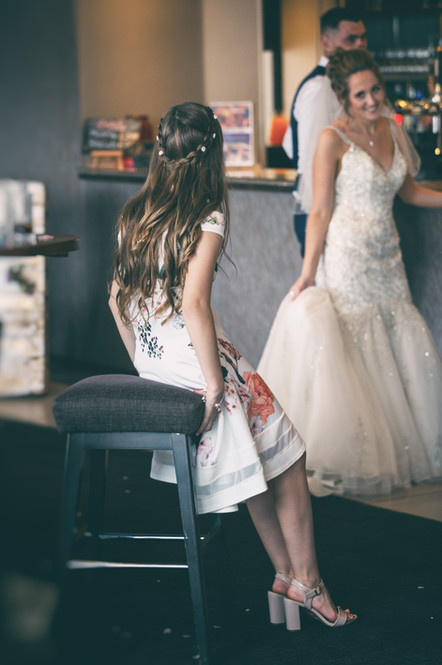 Bride holding her dress whilst talking to a wedding guest at The Mecure Centre Hotel Bedford.