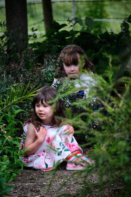 Flower girls hiding in the garden.
