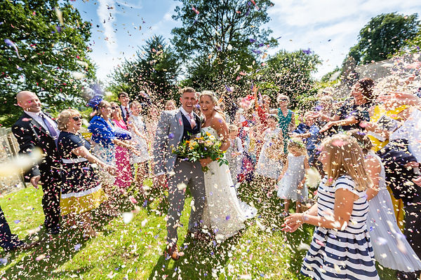 Wedding guests throwing confetti over the Bride and Groom in the church grounds on a sunny day.