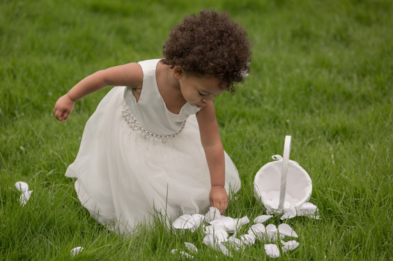 Flower girl picking up petals from the grass.