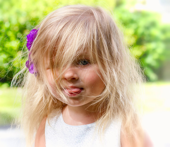 Flower girl with blonde hair sticking out her tongue.