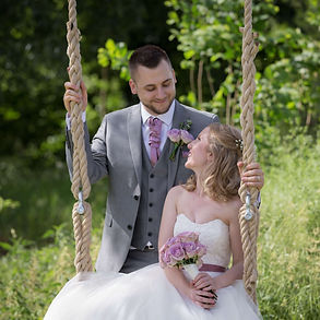 Groom pushing his Bride on a swing in a garden.