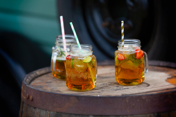 Pimms served in jars with paper straws on an old beer barrel.