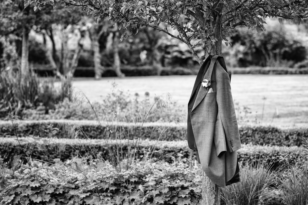 Grooms Jacket hung on a tree.