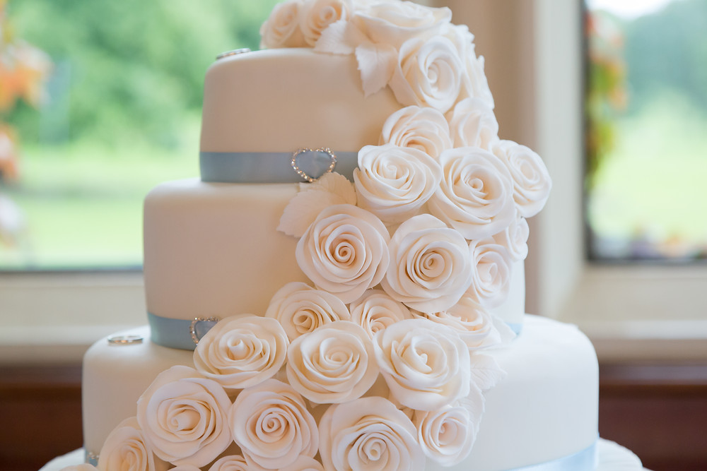 Wedding cake with cascading roses running down the side.