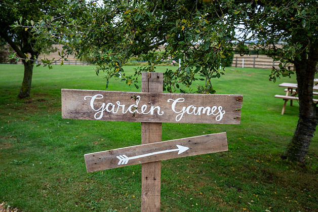 Wooden sign pointing to the Garden Games in an English country garden.